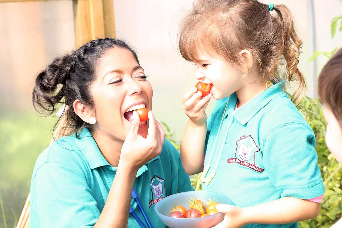 photo of a child and child-minder eating tomatoes