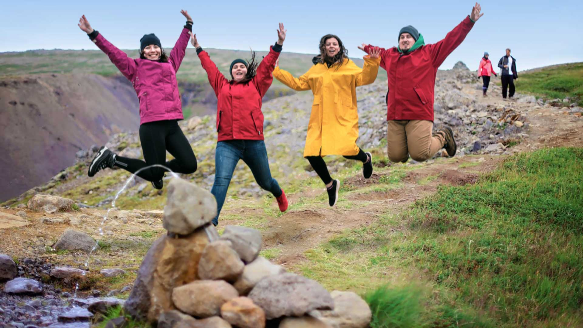 A group of friends jumping into the air after a wonderful hike in Húsafell