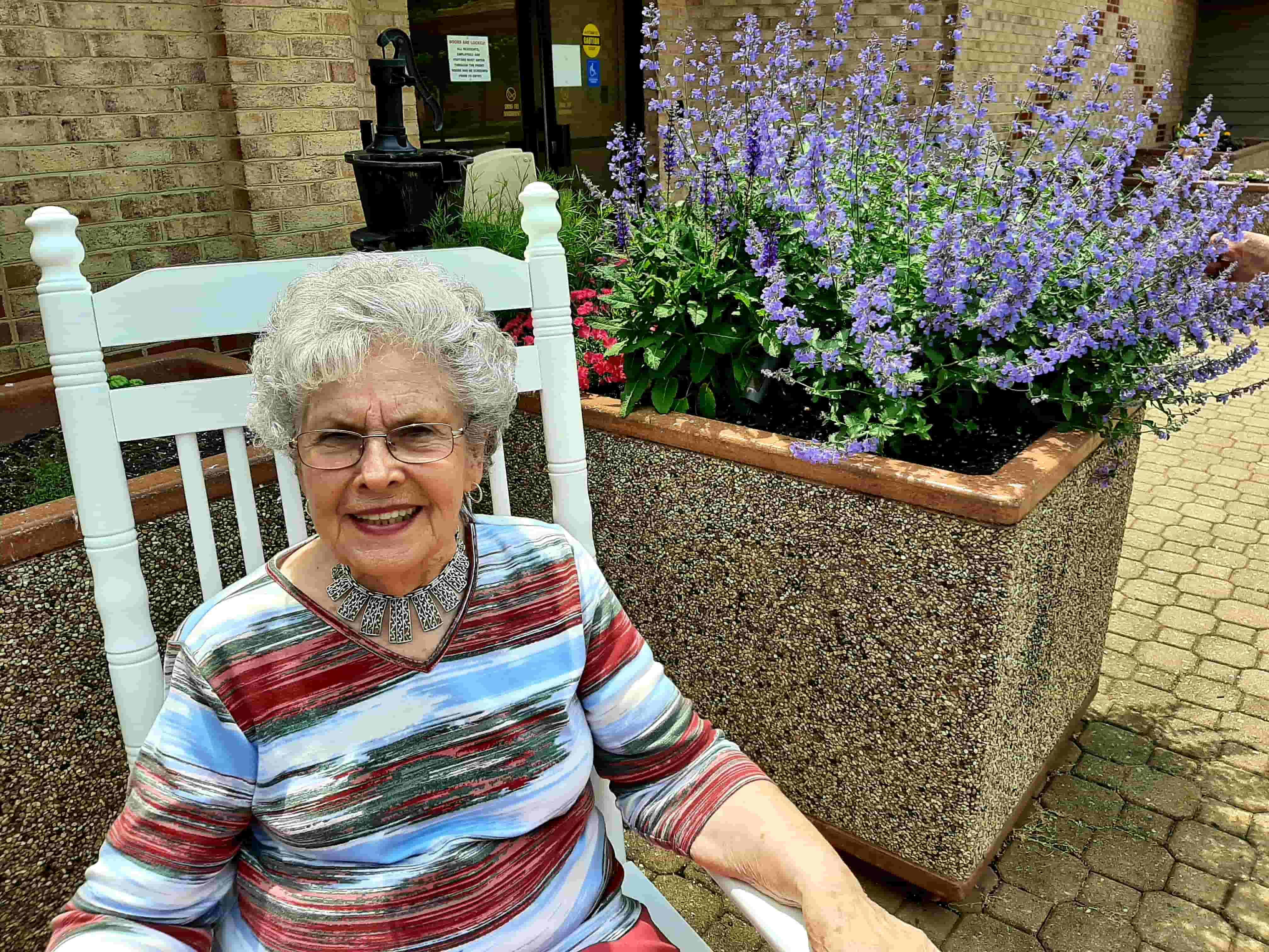 Female senior outside in rocking chair, Friendship resident Ginny Coleman