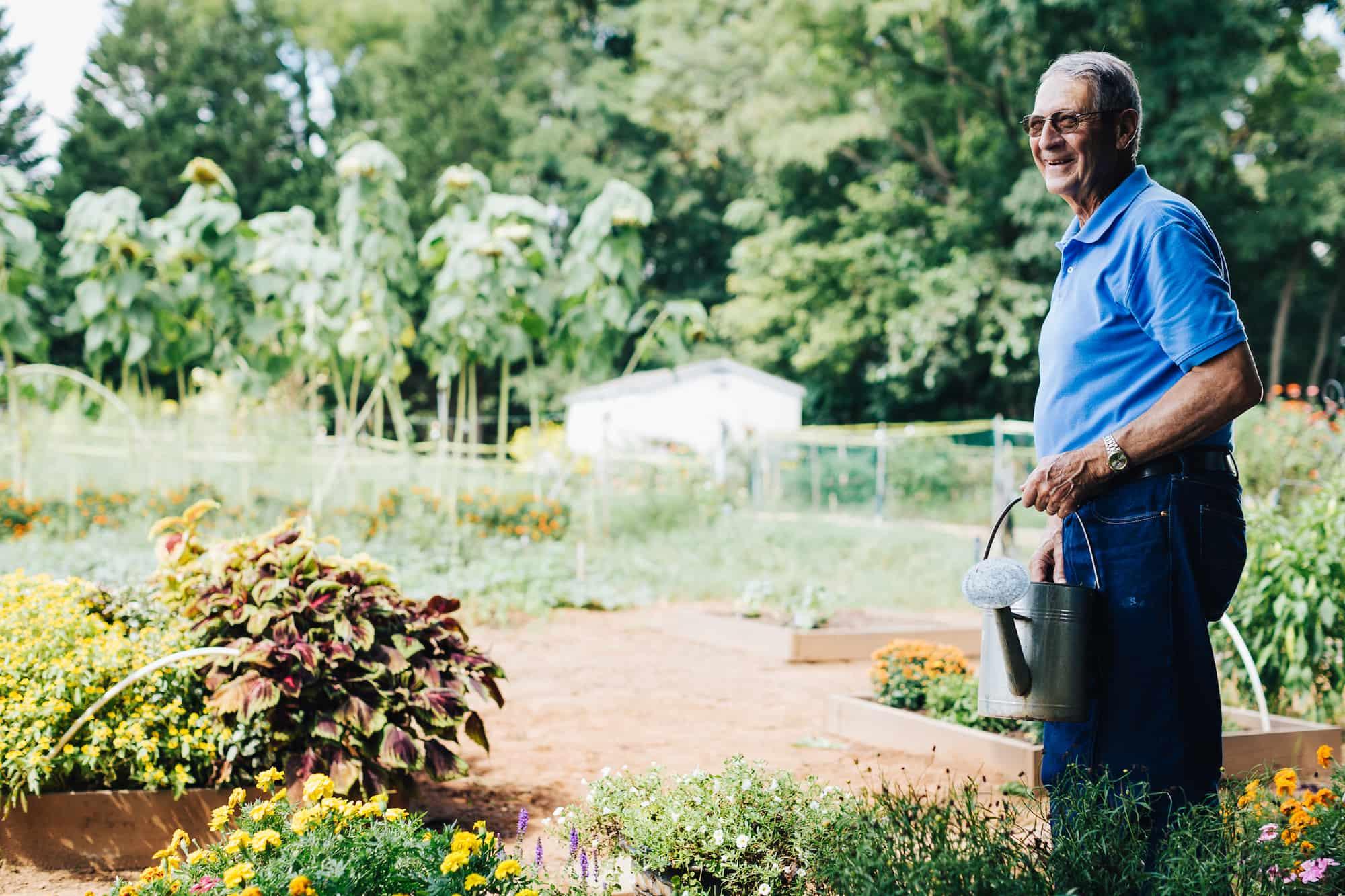 Friendship resident Phil Dean, senior in garden, man watering flowers