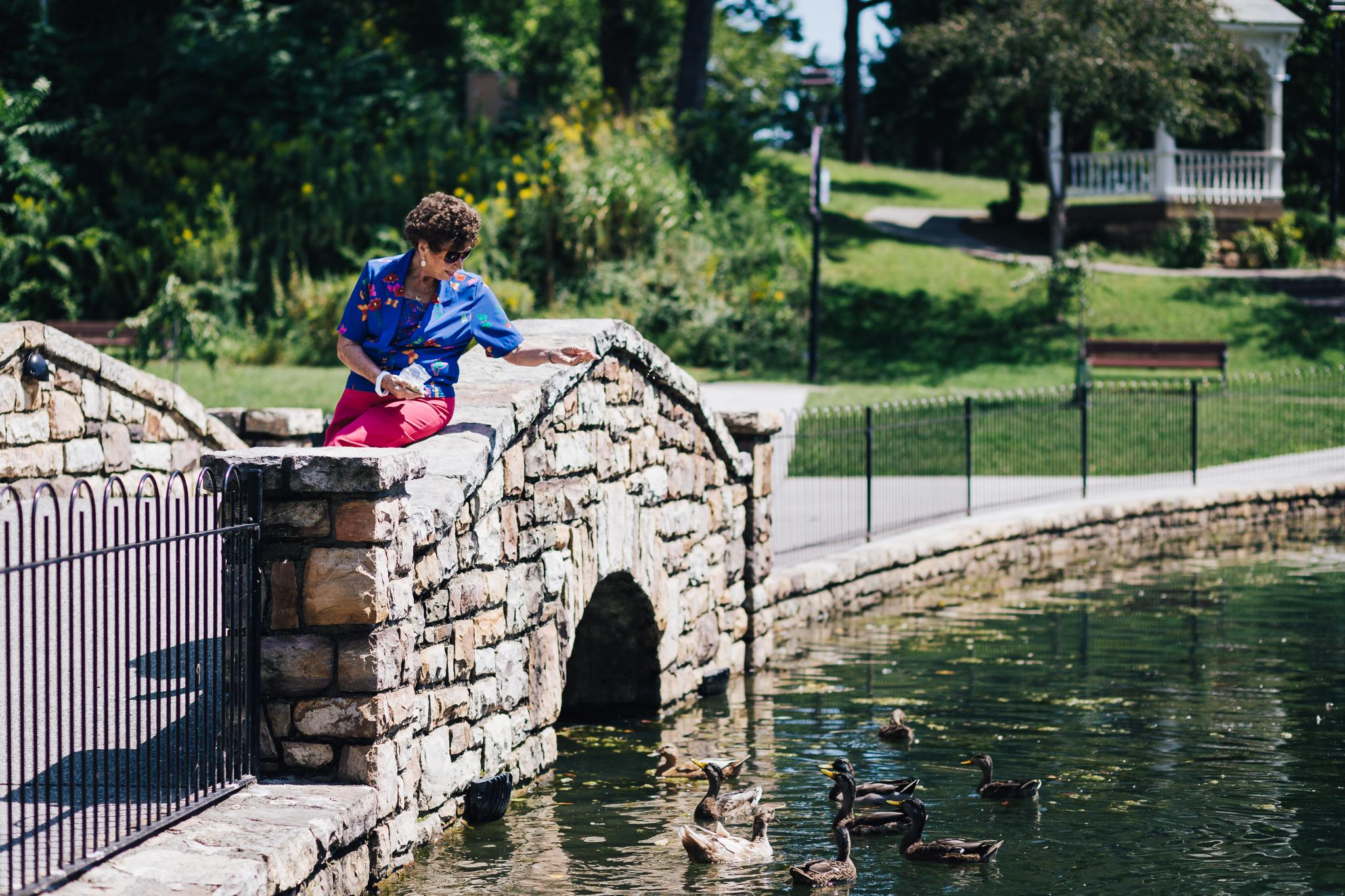 Senior, outdoors, Bridge, lady feeding ducks, Friendship resident