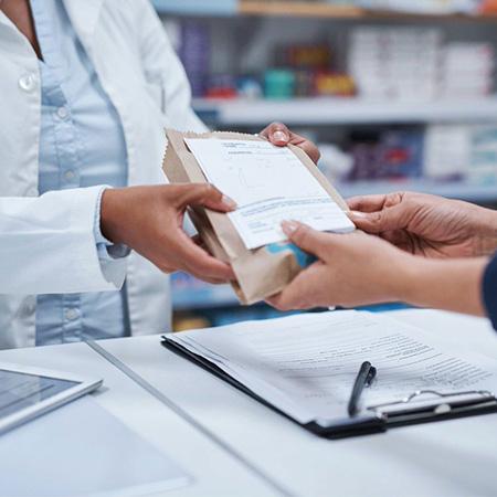 Pharmacist handing a customer a prescription package
