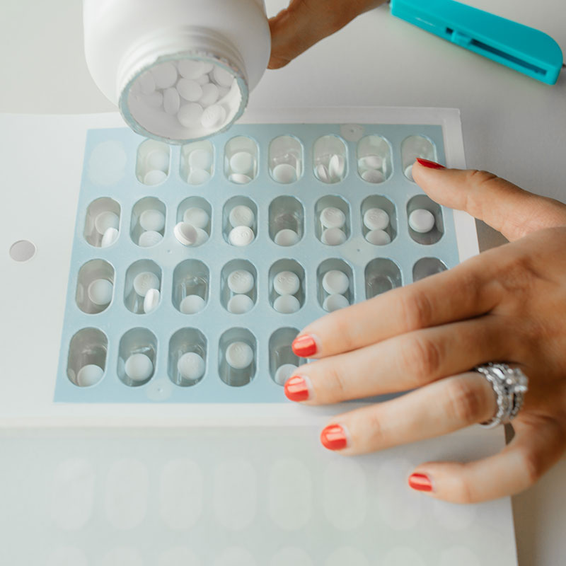 Pharmacist organizing medicine pills into a blue compliance package