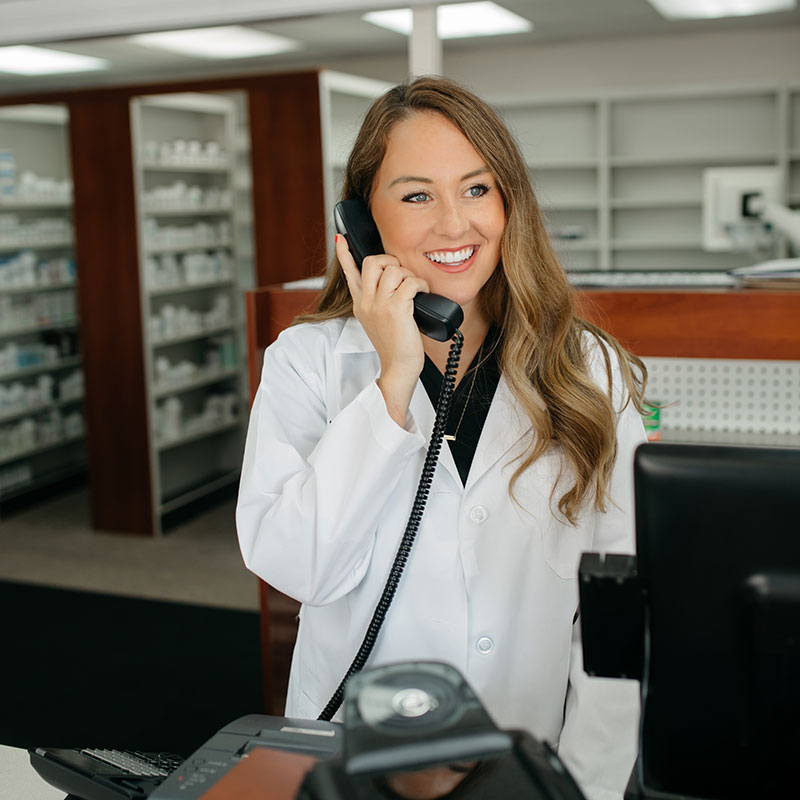 Dr. MeLeigha Milby on the phone smiling inside of Hometown Pharmacy helping a customer