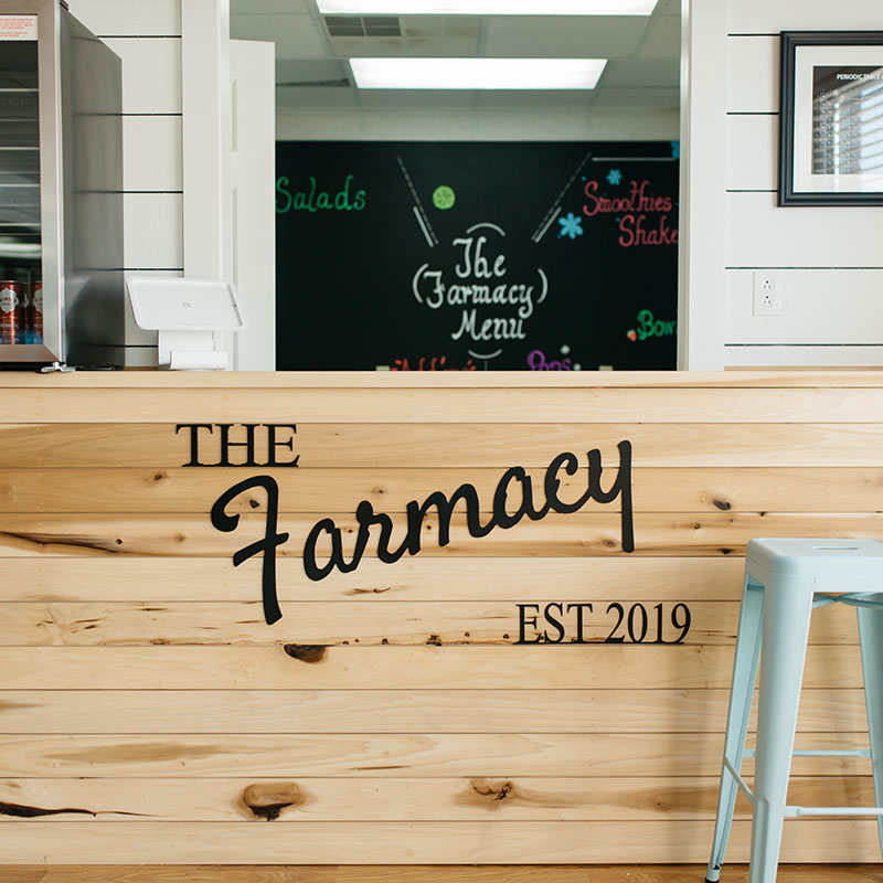 The Farmacy Bar wooden counter with a faded menu in the background