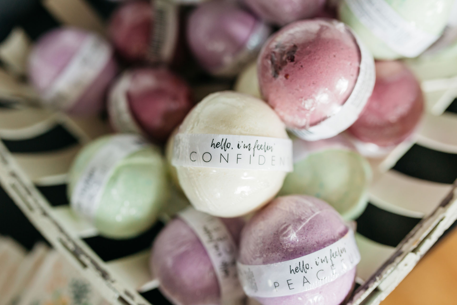 "Bath bombs in a pile that say encouraging words such as ""Hello, I'm feeling Confident."""
