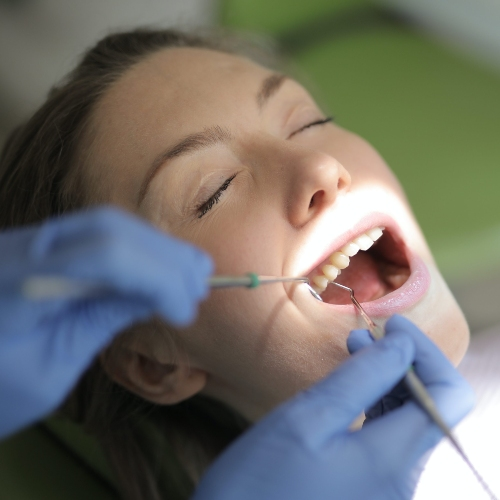 Woman closing her eye and getting her teeth cleaned