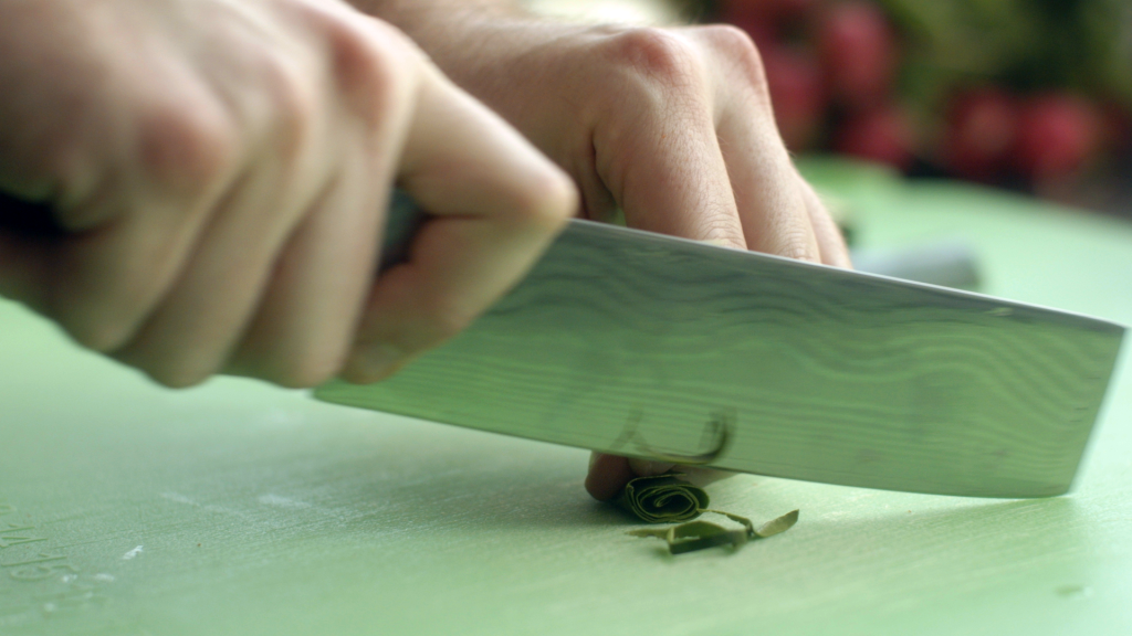Chef Chris Scott chopping kaffir leaves, which are added to the coconut-green curry. | Credit: Freshly