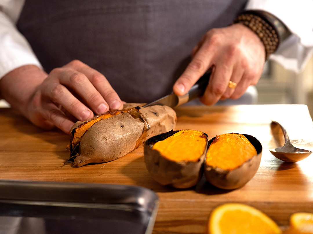 Closeup of Chef Sean Brock slicing open a whole, oven-roasted sweet potato from his Southern-Inspired Pork Chop for Freshly.