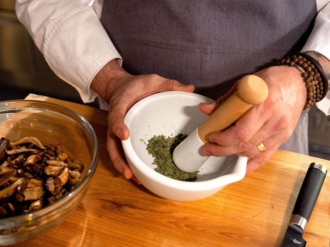 Chef Sean Brock grinds down dried sassafras leaves in a mortar and pestle.