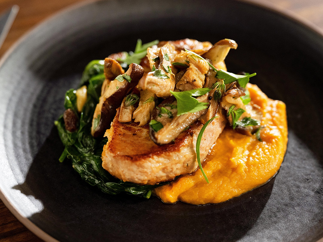 Closeup of Chef Sean Brock's vibrant Southern-Inspired Pork Chop for Freshly.