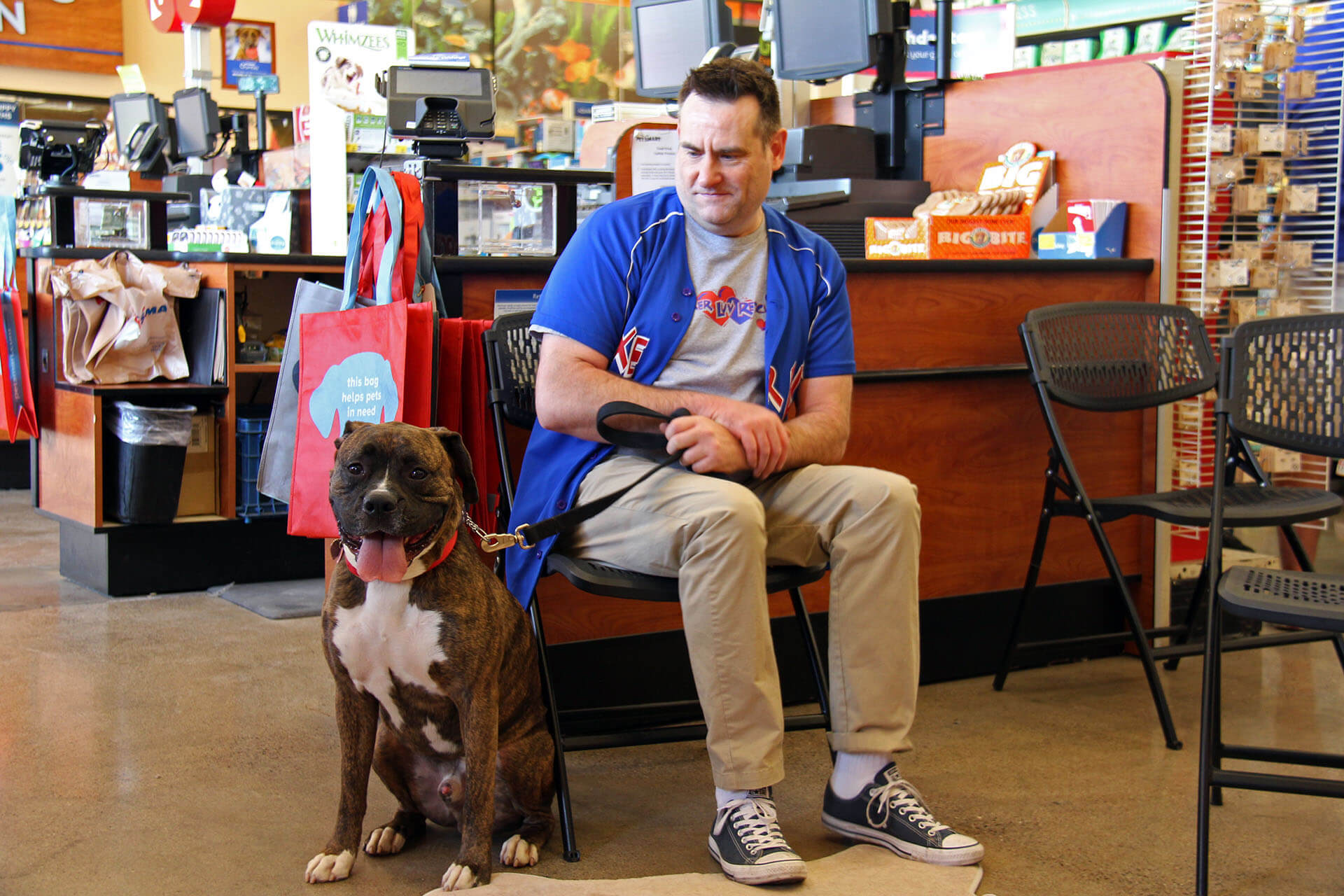 volunteer with boxer at our thrift shop
