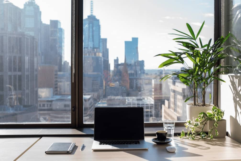 Laptop and coffee on desk with views of Melbourne CBD
