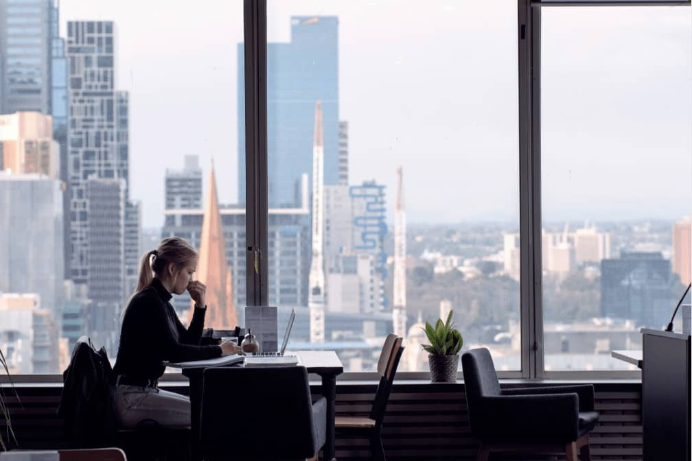 Blonde woman working from cafe with views of Melbourne CBD