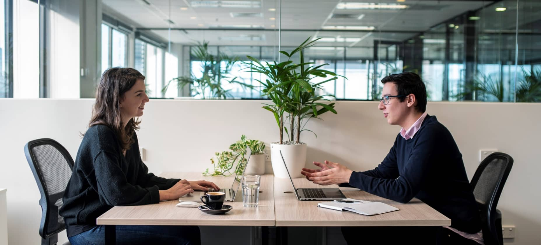 Smartly dressed woman and man working opposite each other in light filled private office
