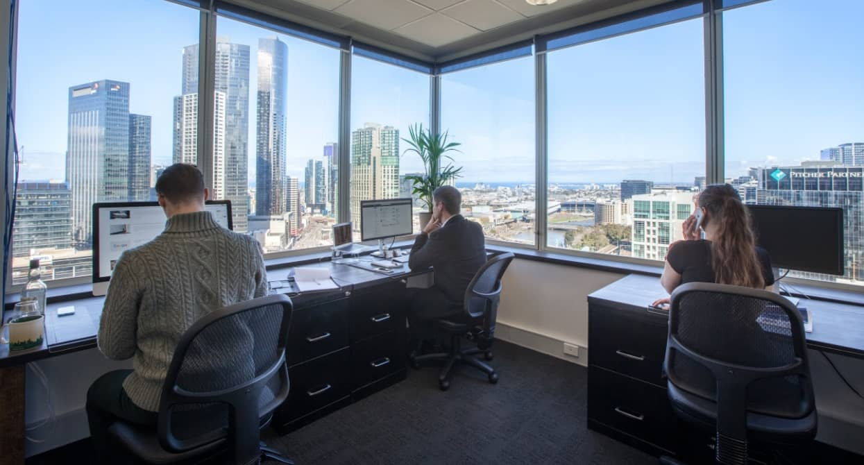 Three employees working from a serviced office with views of Melbourne CBD