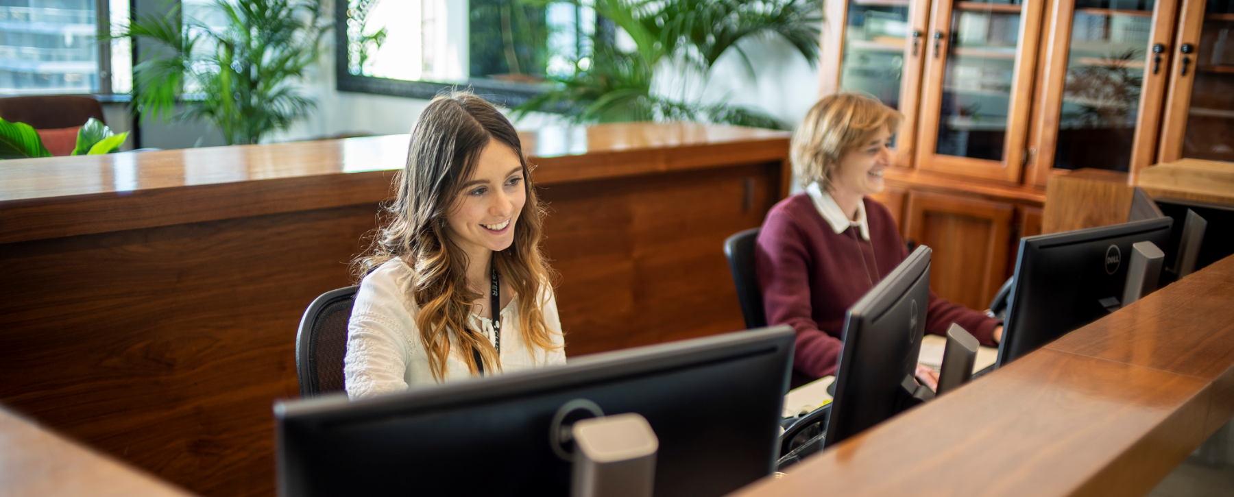 Two smiling receptionists sat behind the front desk
