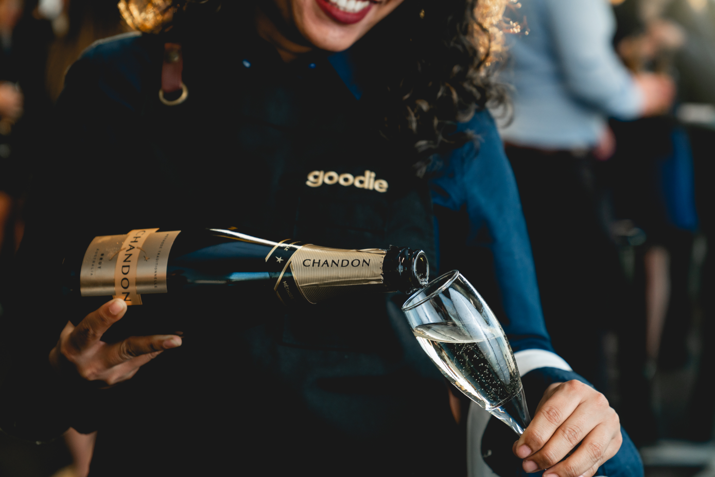 A smiling woman pours a glass of champagne