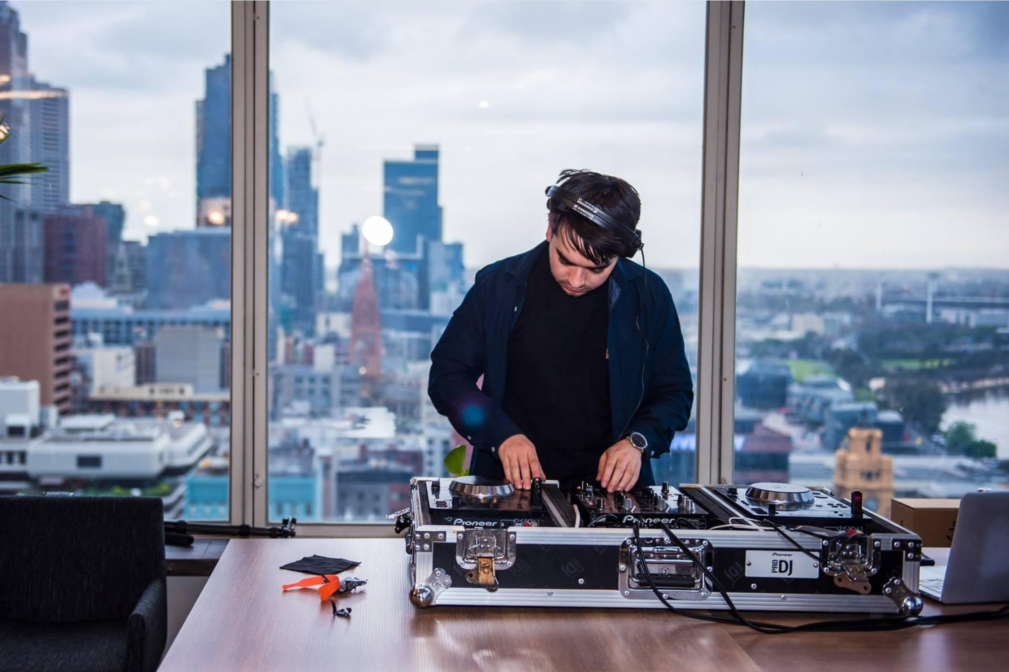 A DJ djing in front of the view of Melbourne's CBD