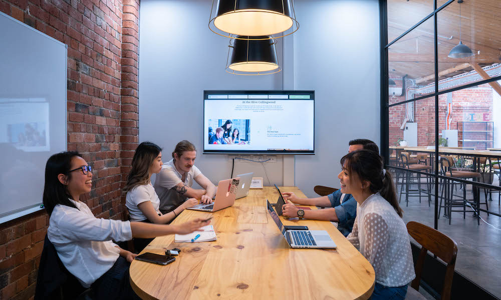 A group of 5 trendy professionals gathered around a large wooden table, within a good sized meeting room with exposed brick wall and warm lighting. They are working off of laptops and also have a presentation on display on a TV at the end of the Table.
