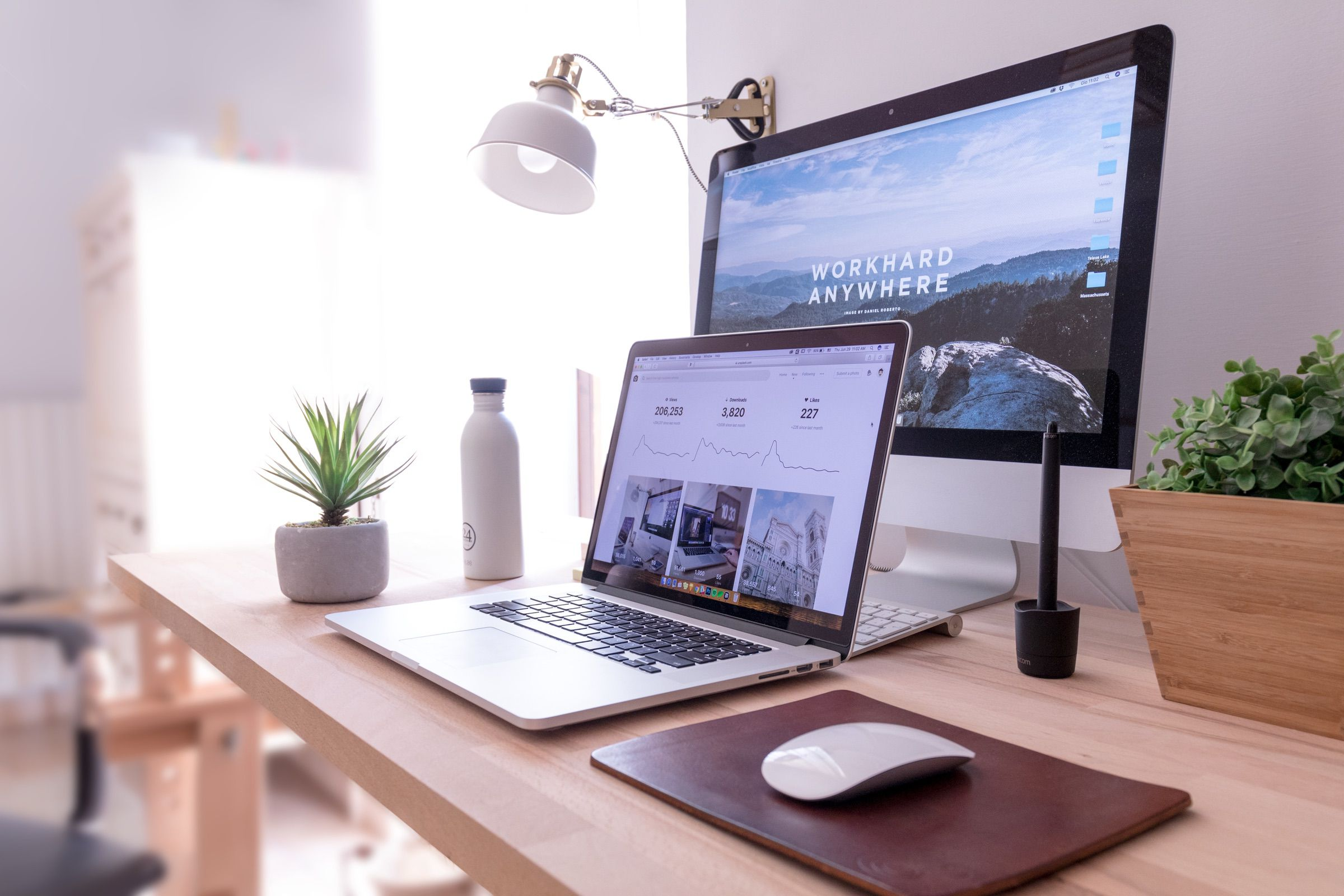 A laptop and a screen on a desk with a lamp and a plant