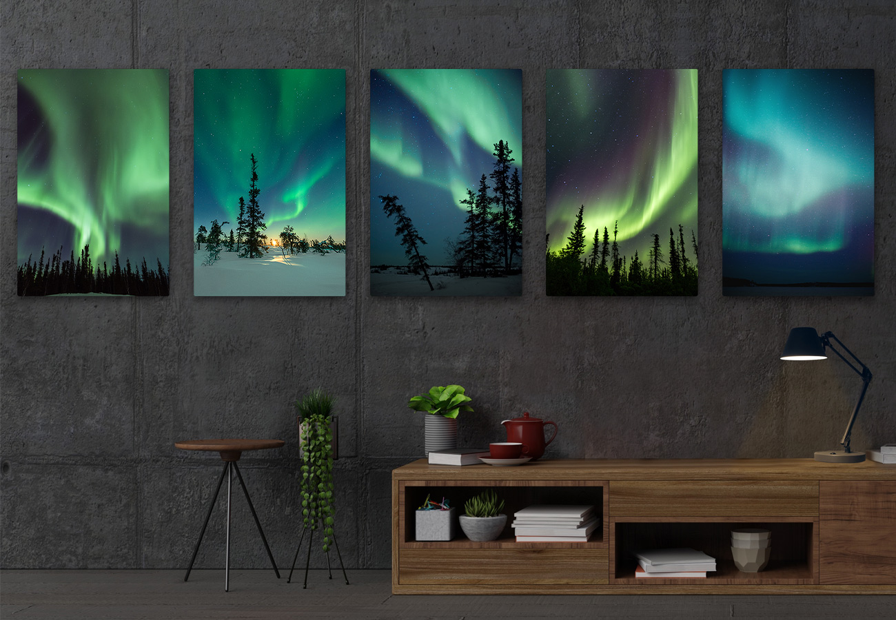 Modern living room with dark wall showing sample of aurora photos.