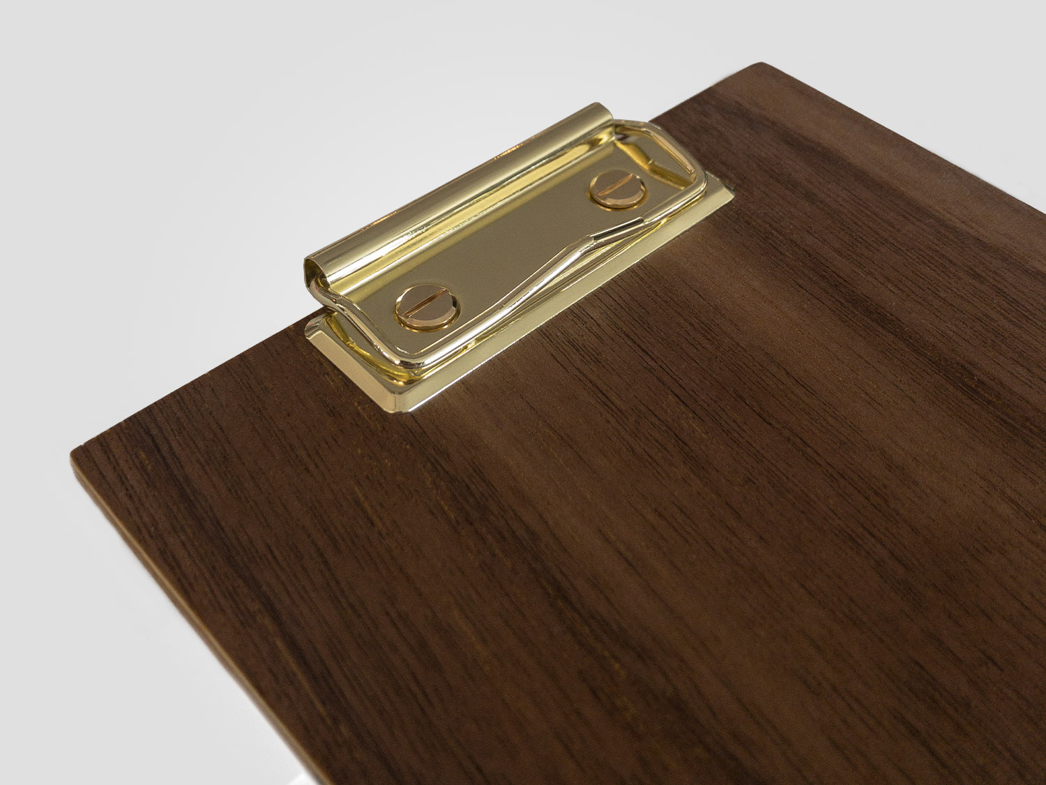 Photo of sample walnut desk calendar with brass coated clip.