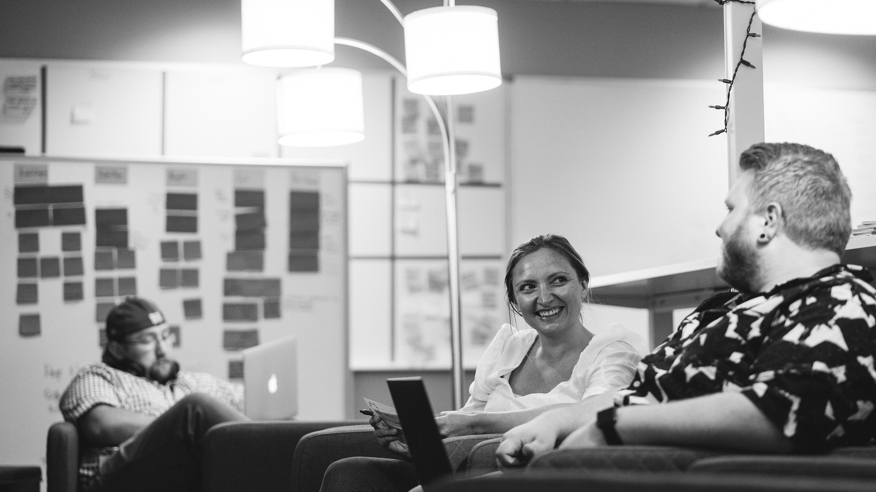 Young man and woman sitting in comfortable chairs smiling and collaborating