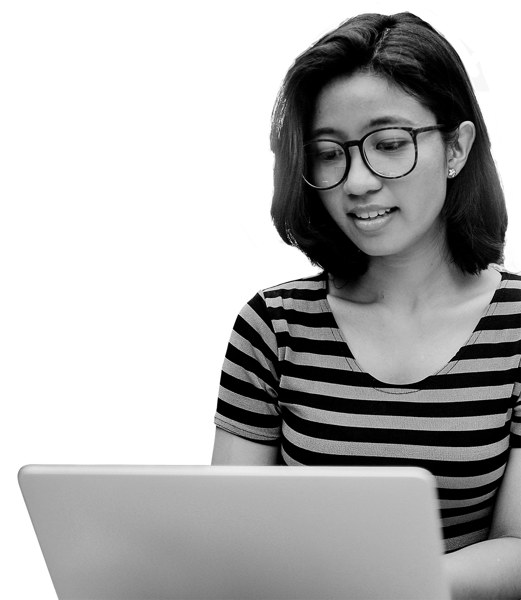 Asian woman with glasses sitting in front of laptop