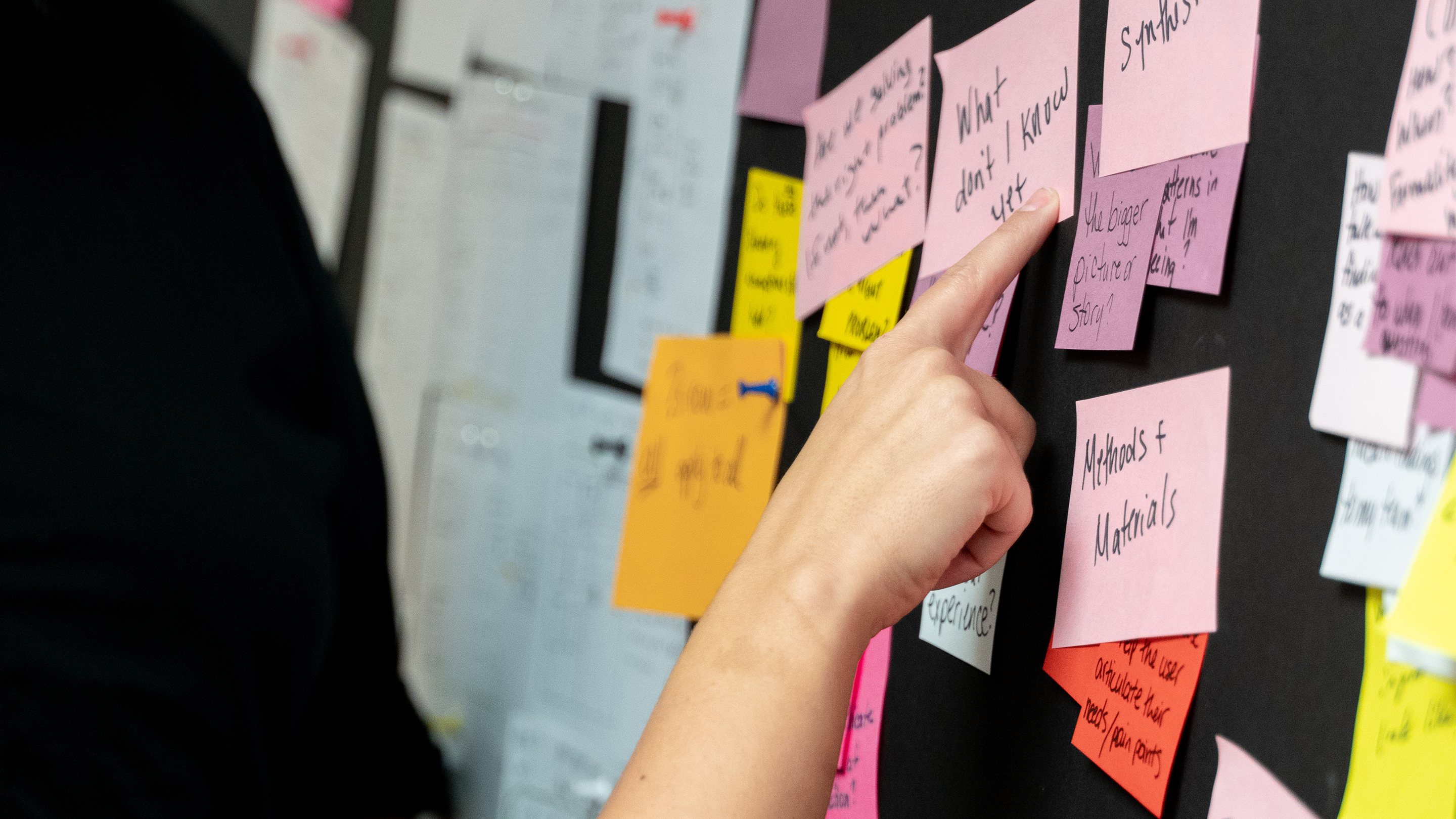 Hand pointing to wall of sticky notes