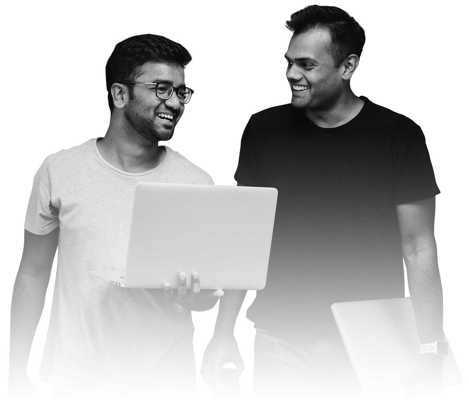 Two Indian young men holding a laptop computer and smiling