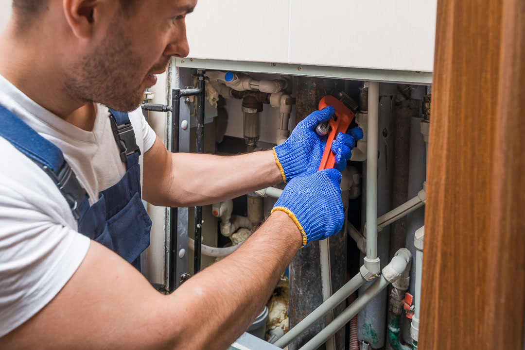 picture of plumber with wrench fixing some pipes
