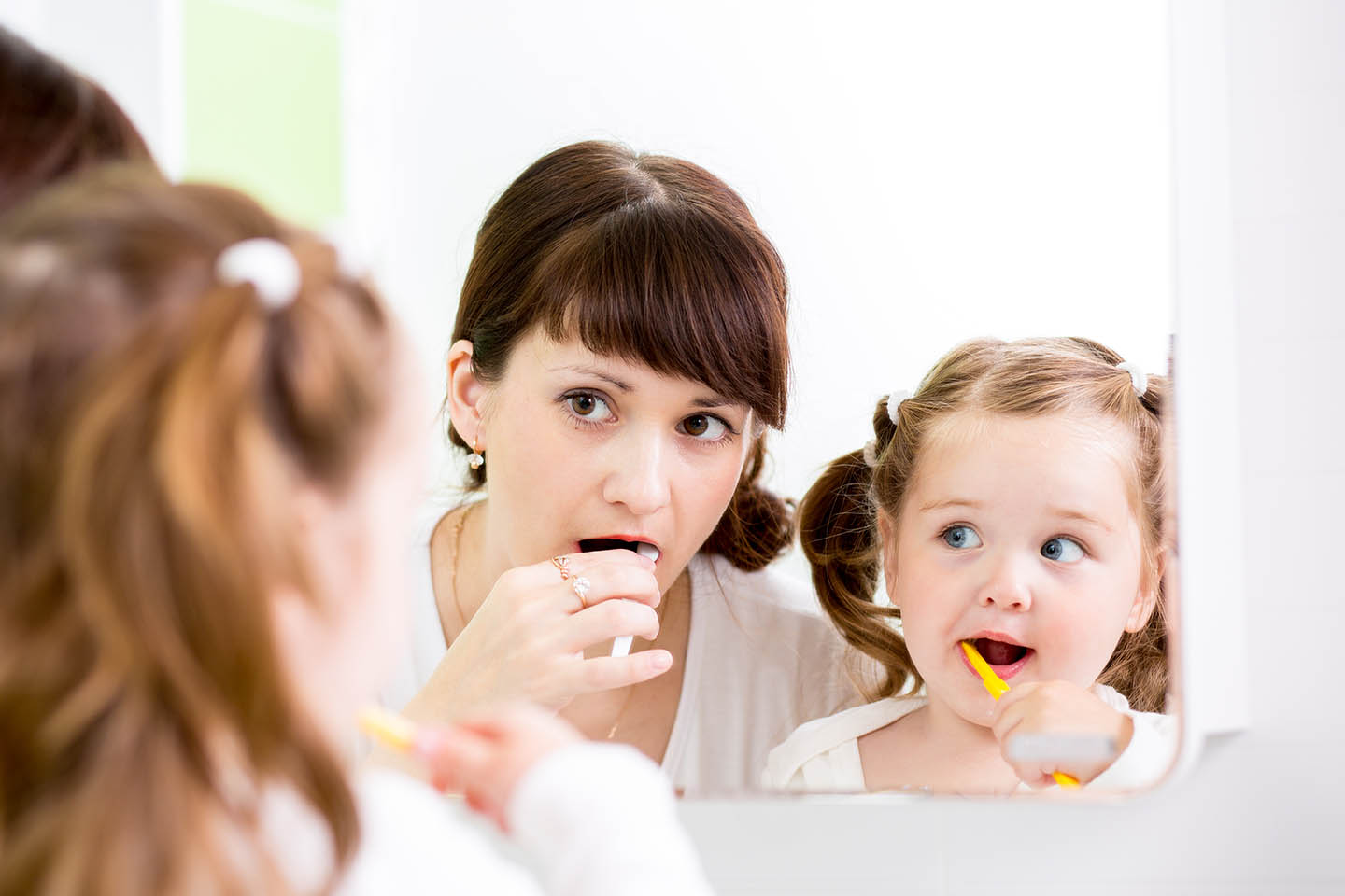 A family practicing brushing teeth