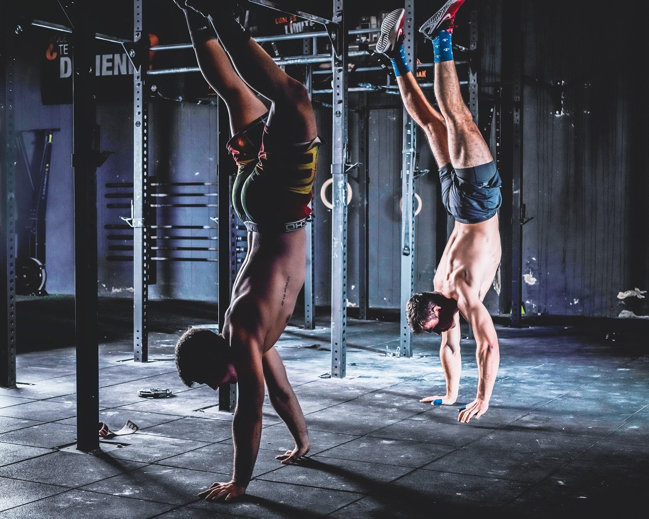 Fotos de estilo contemporáneo de dos atletas de crossfit haciendo paradas de manos