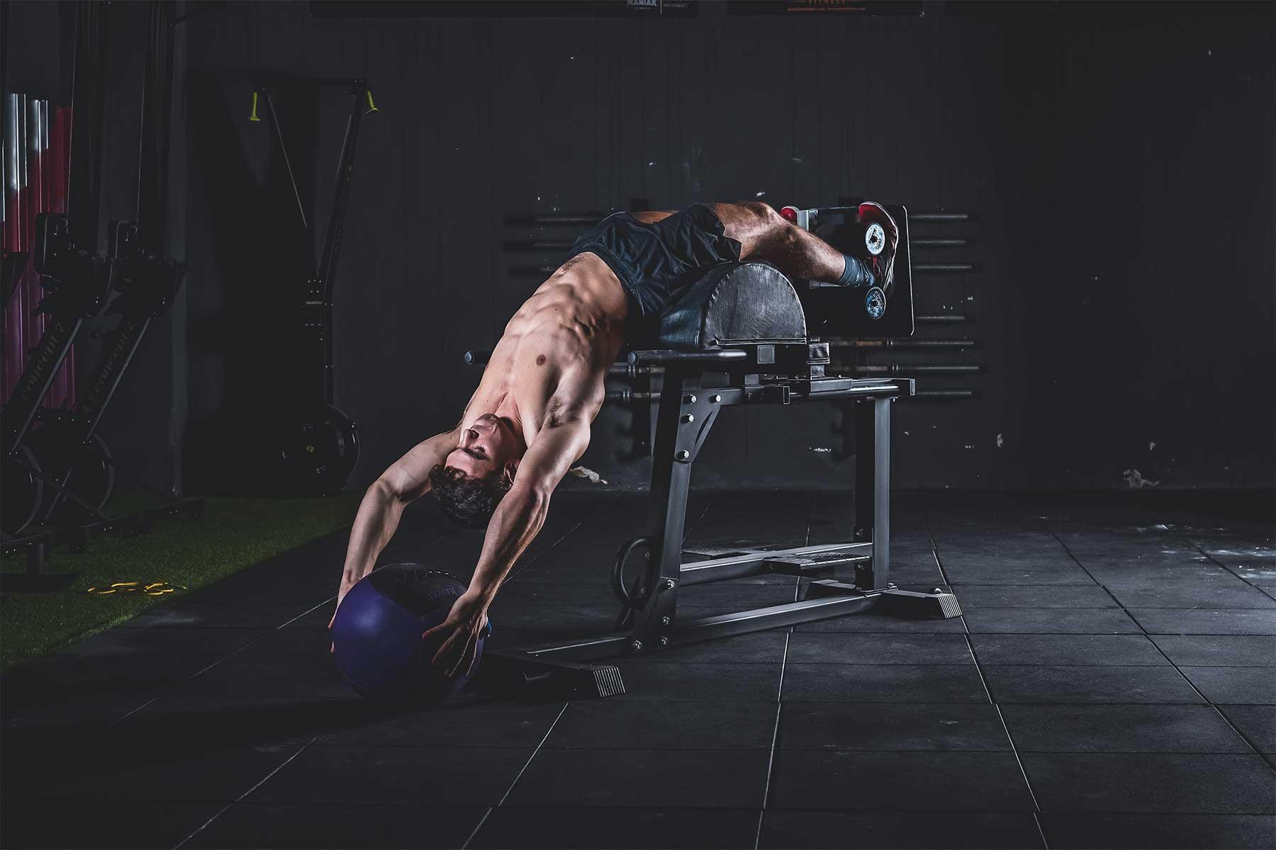 sesión de fotos deportivas de hombre musculoso en el gimnasio levantando una pelota pesada