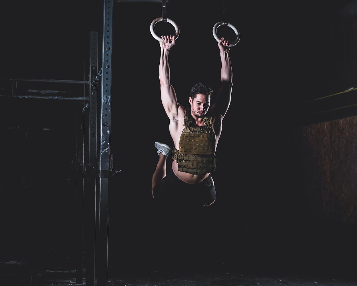 sesión de fotos deportivas de hombre musculoso colgando de anillos de gimnasio