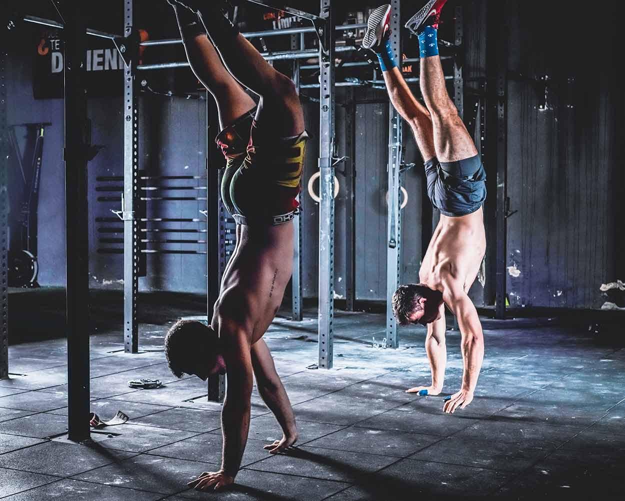sesión de fotos de publicidad de gimnasio de dos hombres caminando en las manos
