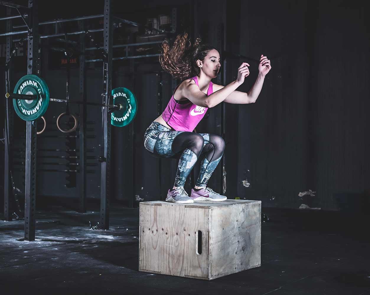 Sesión de fotos de publicidad de gimnasio de una mujer joven saltando sobre una caja de madera