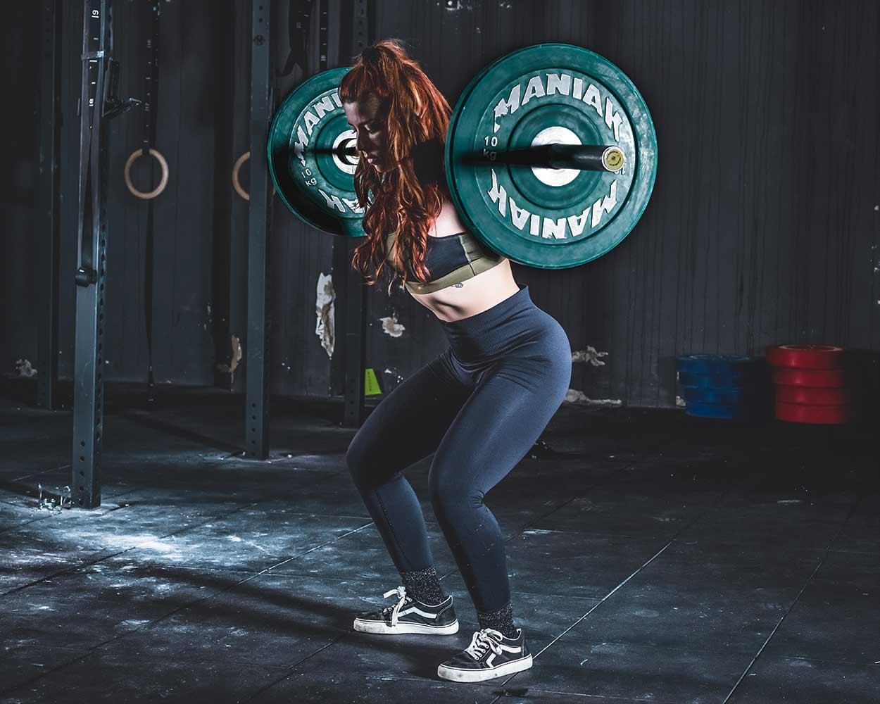 Sesión de fotos de publicidad en el gimnasio de una mujer joven que levanta una barra pesada