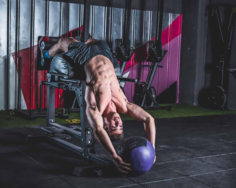 Sesión de fotos de publicidad de gimnasio de un hombre musculoso levantando una pelota pesada
