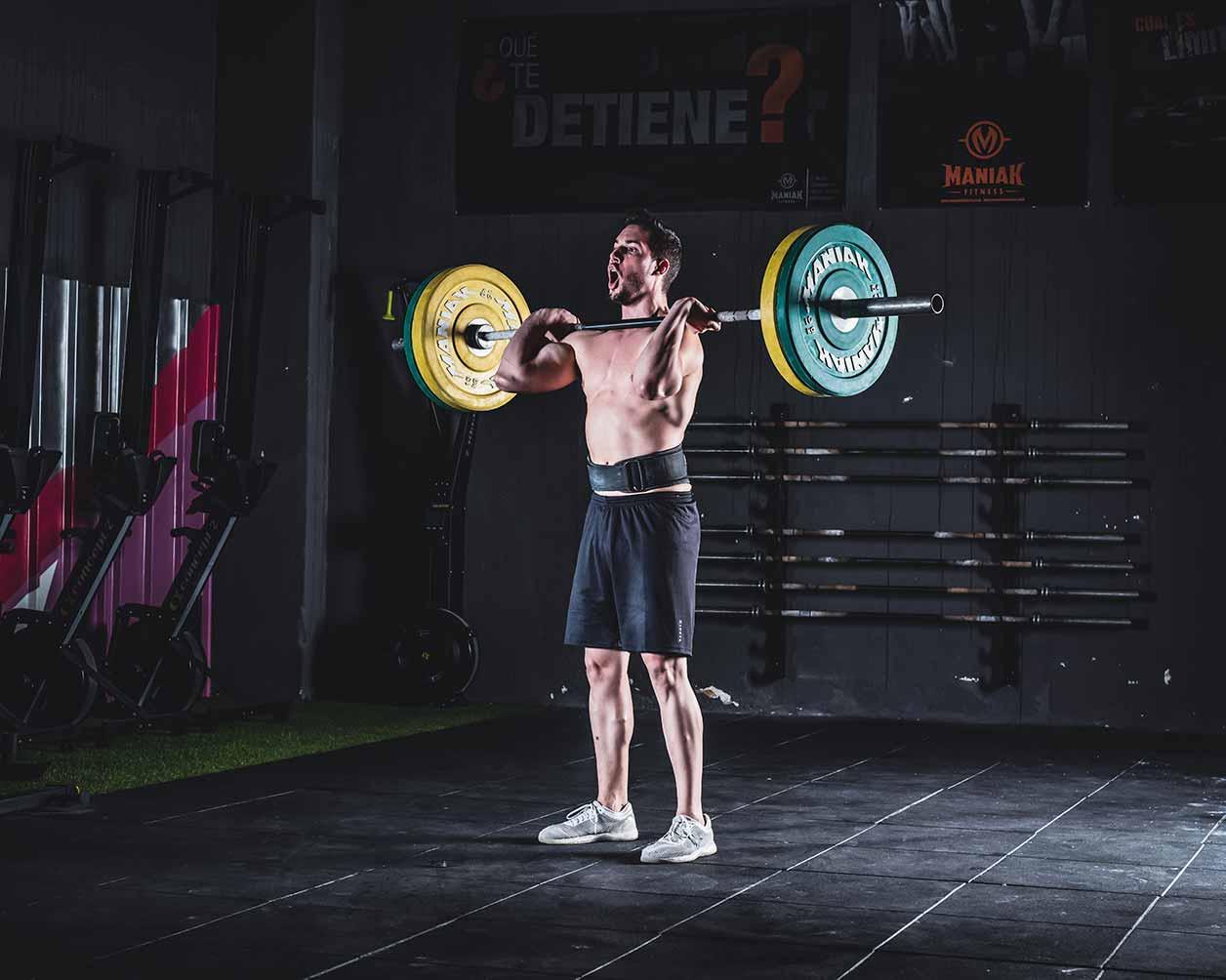 Sesión de fotos de publicidad en el gimnasio de un hombre musculoso levantando una pesada barra