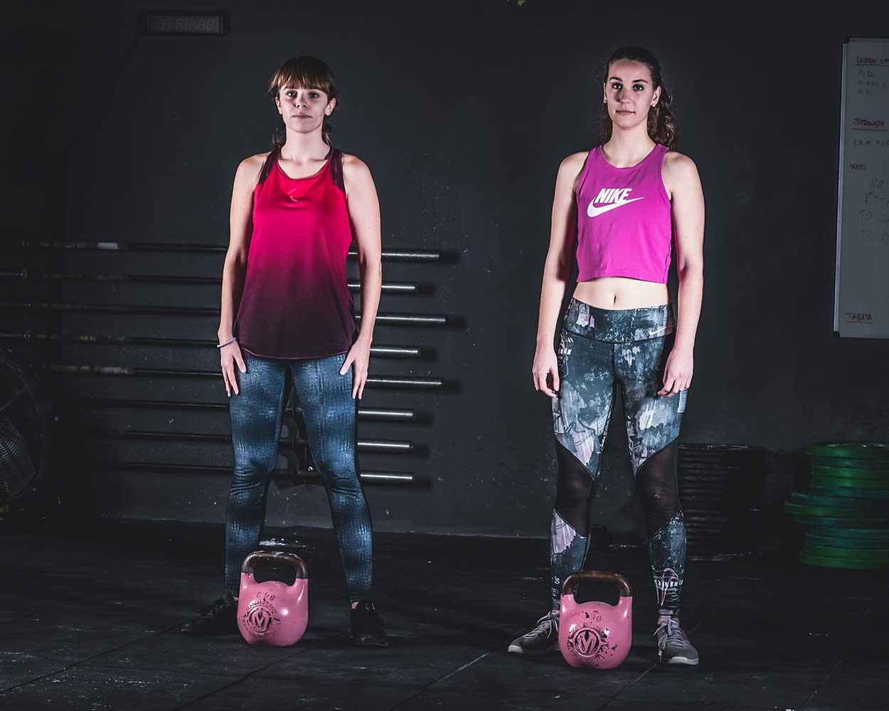 Gimnasio publicidad sesión de fotos de dos mujeres jóvenes en ropa deportiva mirando a la cámara.