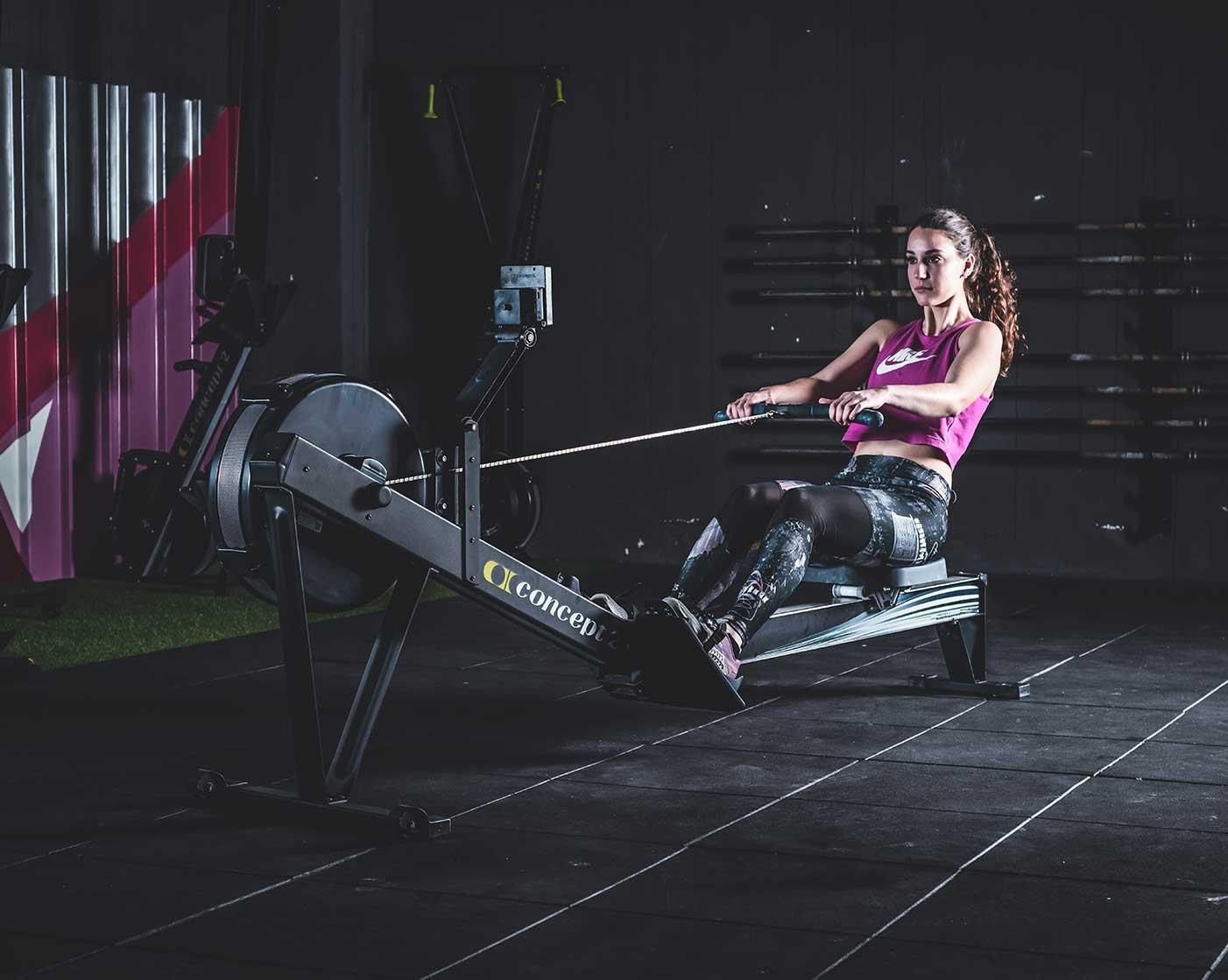 sesión de fotos de publicidad de gimnasio de mujer en máquina de remo