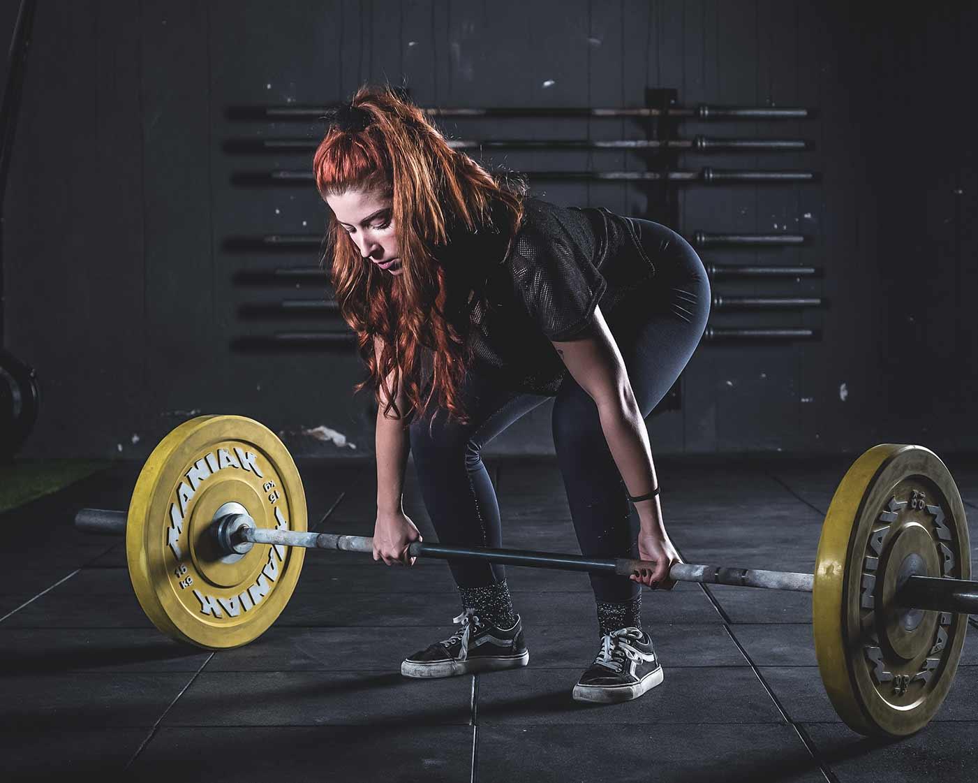 sesión de fotos de publicidad de gimnasio de mujer preparándose para levantar pesas