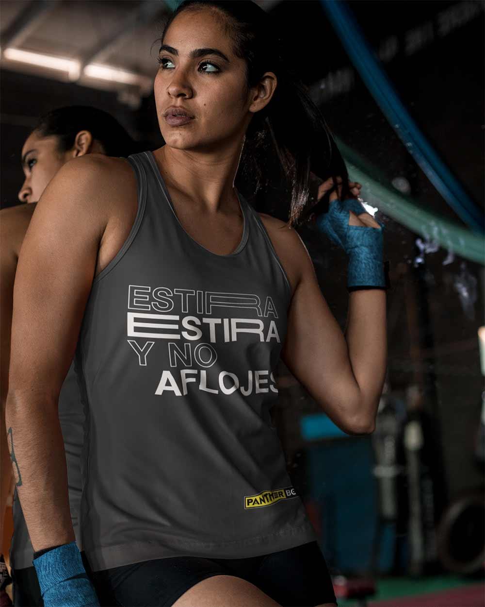 La mujer joven se coloca en gimnasio con una camisa gris y un diseño fresco de la camiseta.