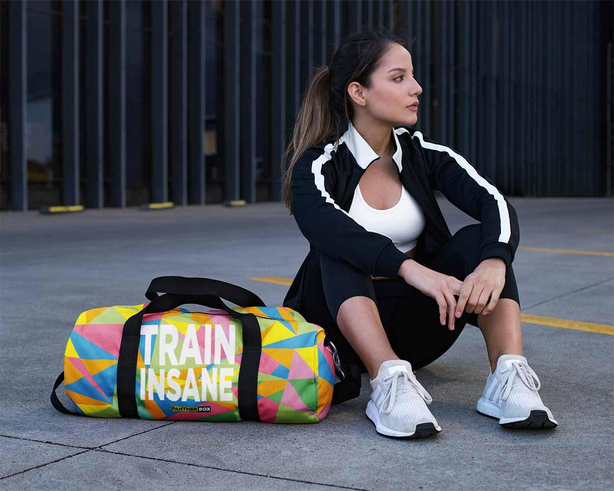 Mujer joven en ropa deportiva sentado junto a una colorida bolsa de deporte