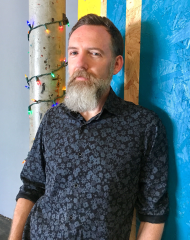 Tom Illmensee (and beard) leaning against a striped wall