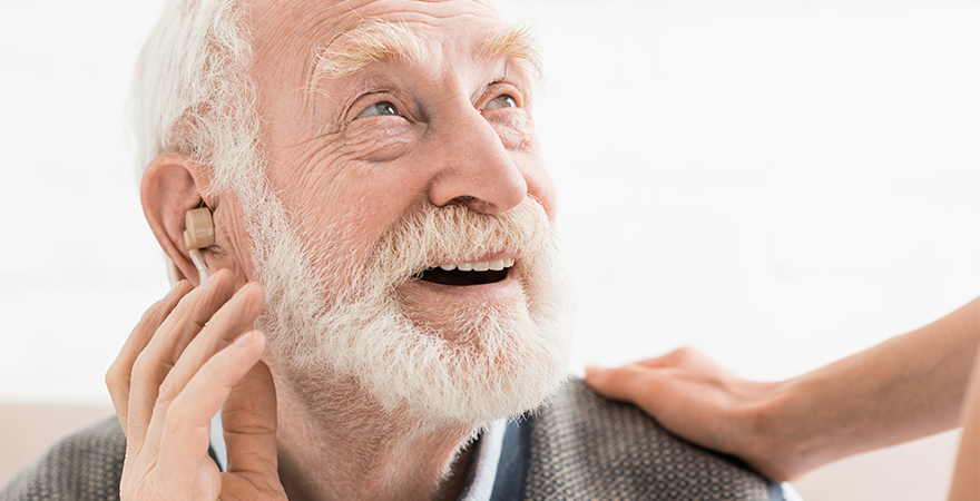 Glad man with hearing aid in ear, looking at friend