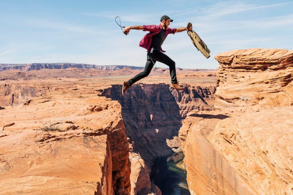 Man jumping over canyon