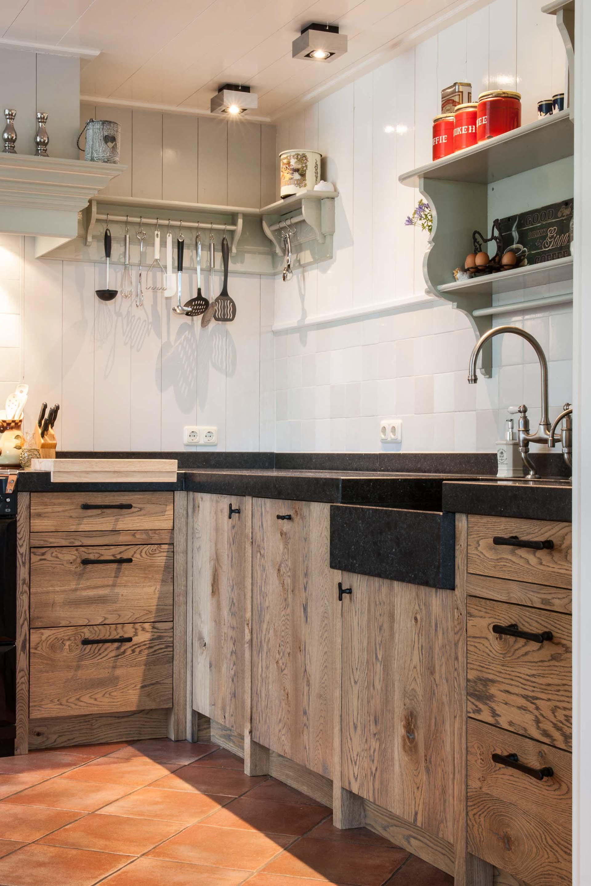 Houten keuken met hardsteen aanrechtblad en klassieke kranen